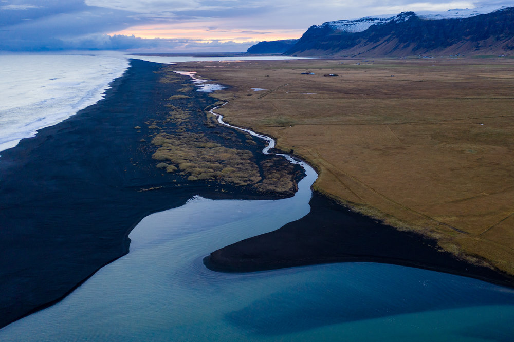 A turquoise-colored stream glows in the afternoon light as a coming storm approaches the barren coastline of southern Iceland.