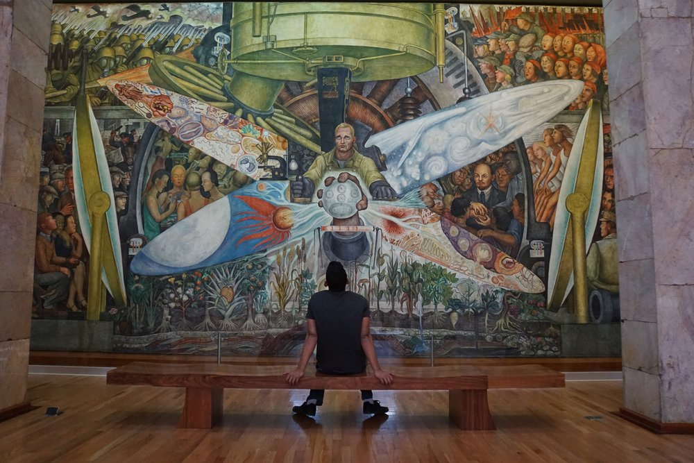 An onlooker stares up at one of diego rivera's most famous pieces, housed in the museo del palacio de bellas artes.