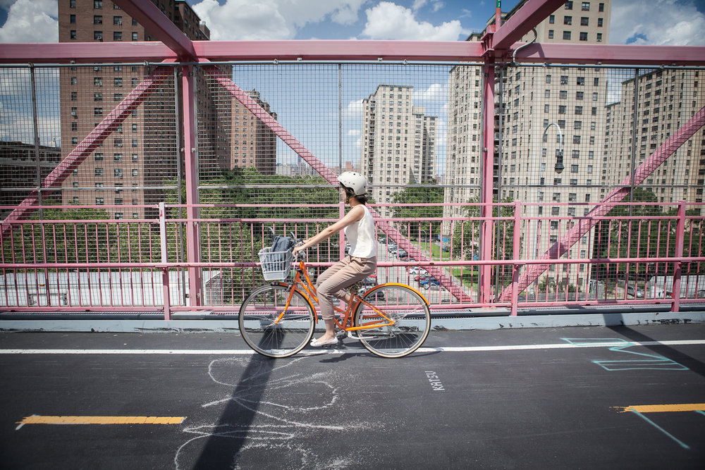 Woman riding her bike on the Williamsburg Bridge, New York