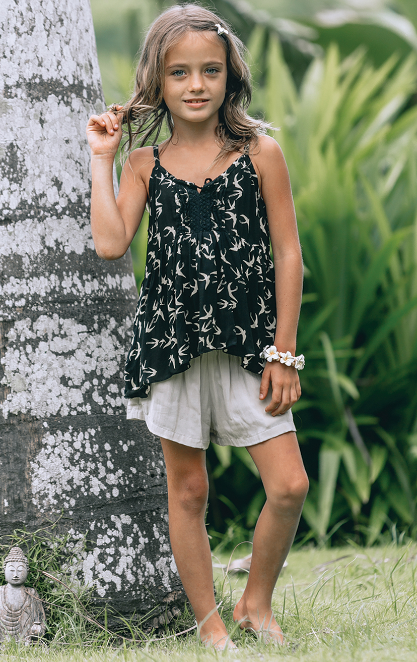 TOP NIKITA   Spaghetti strap top, center lace detail, pom pom ties  RAYON VOILE | 2/3 | 4/5 | 6/7 | 8/10   –    SHORTS BAIK   Smocked waist shorts, w/ front pockets  RAYON VOILE | 2/3 | 4/5 | 6/7 | 8/10
