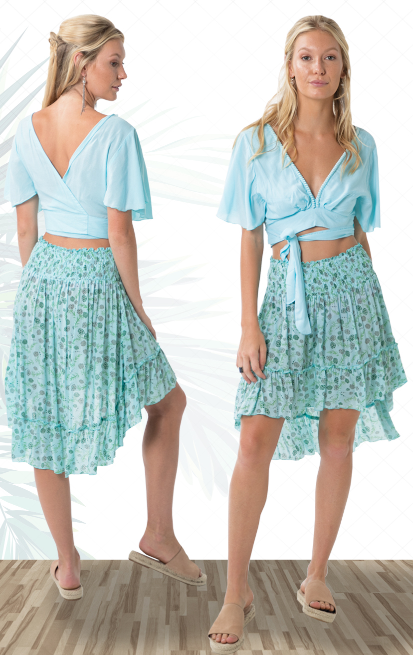 TOP MOSS   S/s v-neck crop top, pom pom neckline trim, wrap around adjustable ties  100% RAYON | XS-S-M-L  –   SKIRT CRYSTAL   Smocked waist  high-low skirt, bottom ruffle  100% RAYON | XS-S-M-L