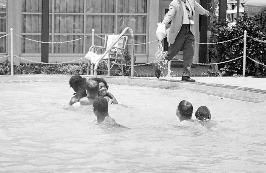 """(Photo AP/JK, 1964)Le directeur d'un hôtel verse de l'acide dans sa piscine """"réservée au blancs"""" lorsqu'il réalise que des afro-américains y nagent."""