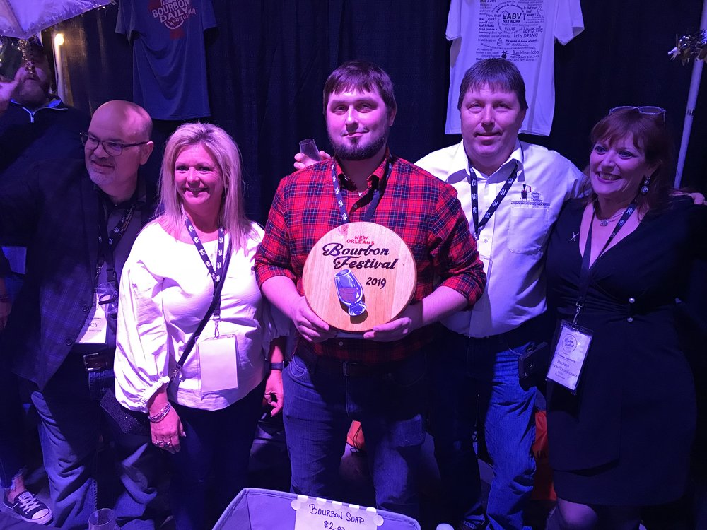 """New Orleans Bourbon Festival organizers Tracy Napolitano (left) and Barbara Hirsch (right) congratulate Michele, Royce and Roy Neeley on their 2nd place award for their bourbon in the """"Under 4-Years"""" category."""