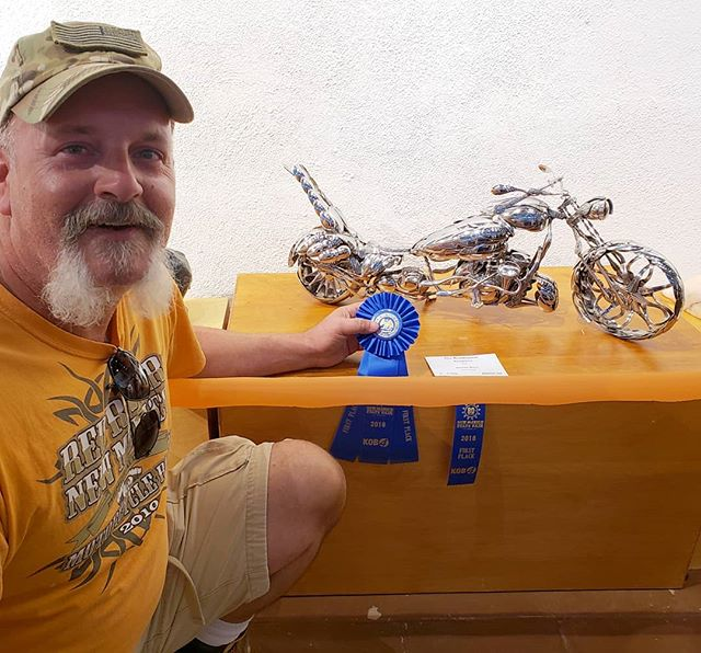 "Another year, another Blue. ""The Roadrunner"" spoon motorcycle took first place in sculpture at the 80th New Mexico State Fair Fine Art Show. Two years in a row. If you're able to stop by, and see it, along with all the other beautiful art, please do. You can't miss it. As you walk in, it's right in front of you, with lights gleaming down on it.  #art #JamesRice #sculpture #metalart #fineart #motoart #motorcycleart #motorcycles #chopper"