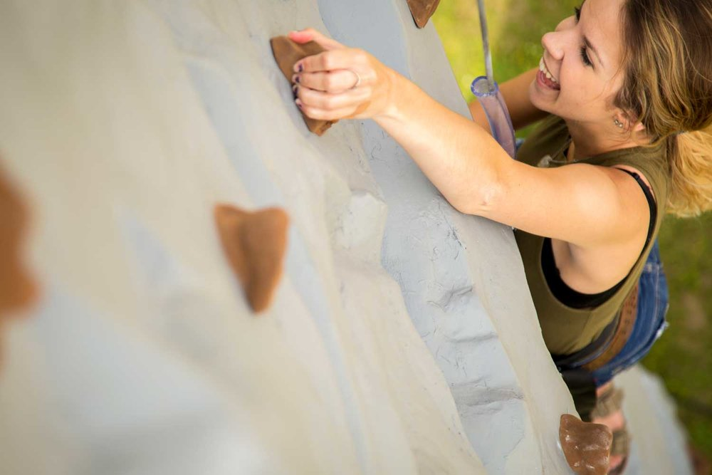 Courtney, from Group Sales, helps Adventure Center Staff train on the new climbing wall.