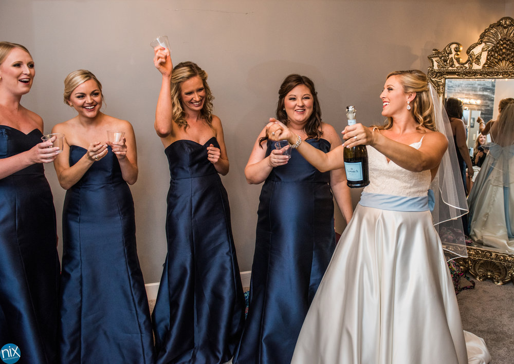 bride pops champaign with bridesmaids View At Emerald Lake .jpg
