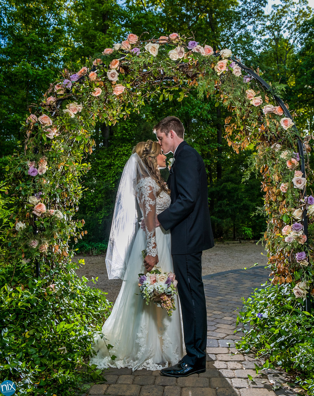 bride and groom under flower arch Morning Glory Farm.jpg
