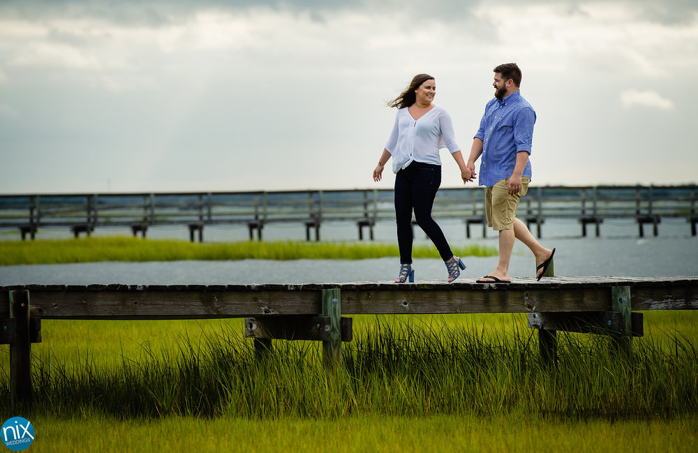 couple_walks_along_dock_emerald_isle_engagement.jpg