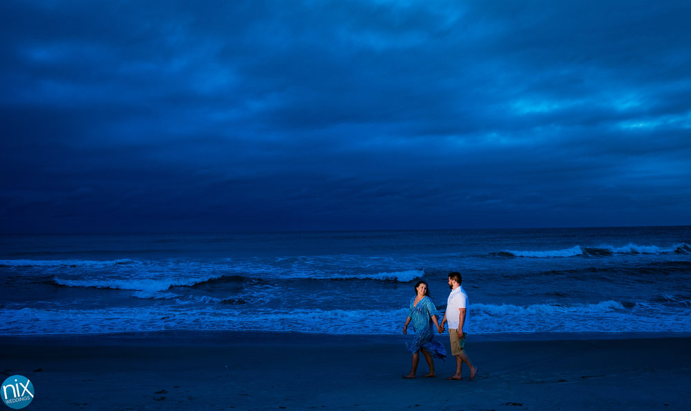 emerald_isle_couple_walks_on_beach_sunset_engagement.jpg