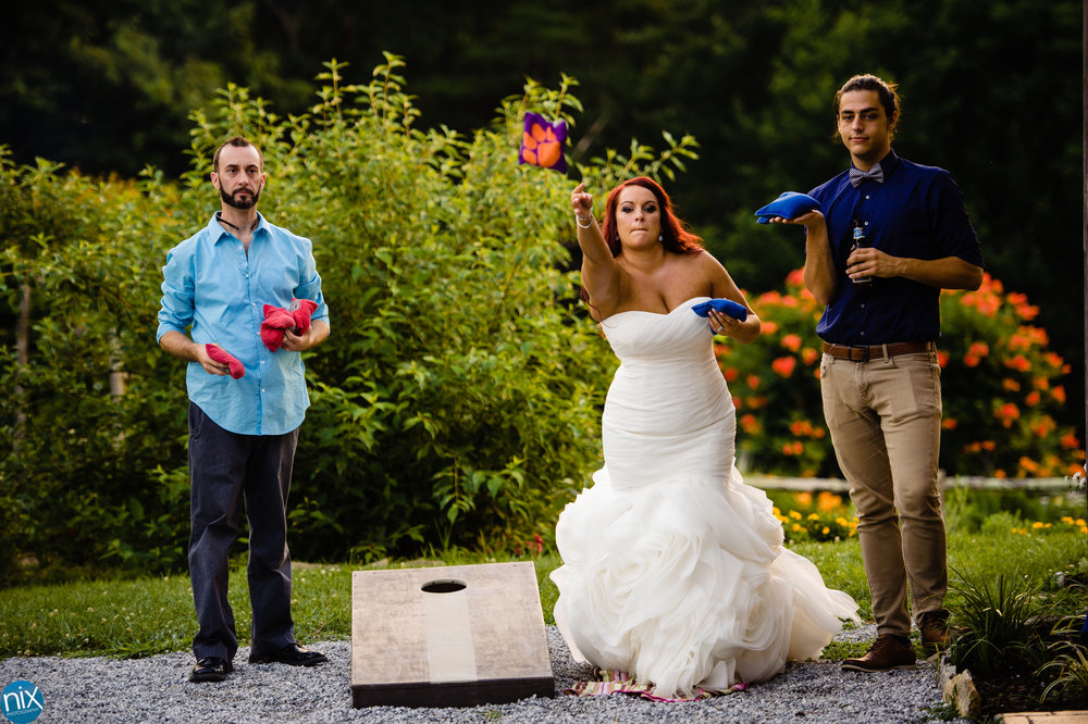 bride plays corn hole during mountain wedding.jpg