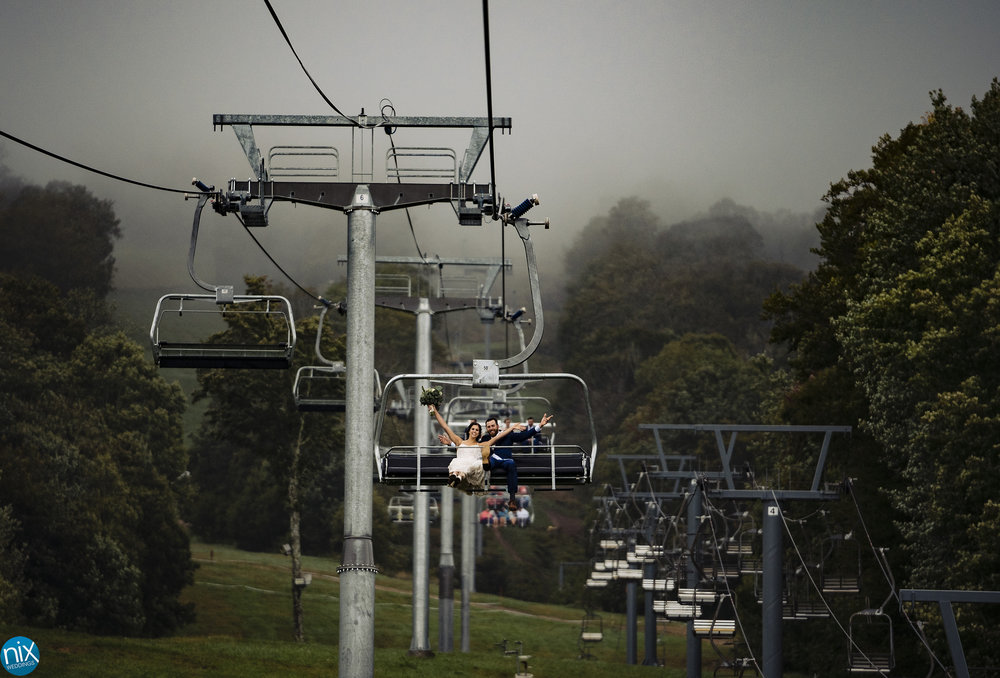 bride and groom ride ski lift after wedding.jpg