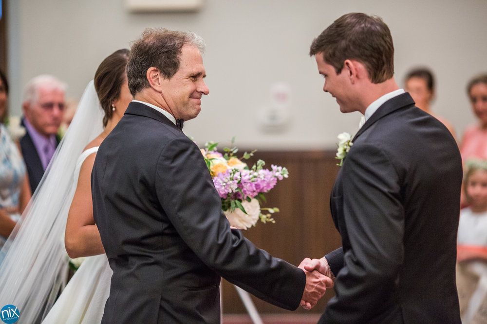 St Peters Catholic Church father shakes hands with groom.jpg