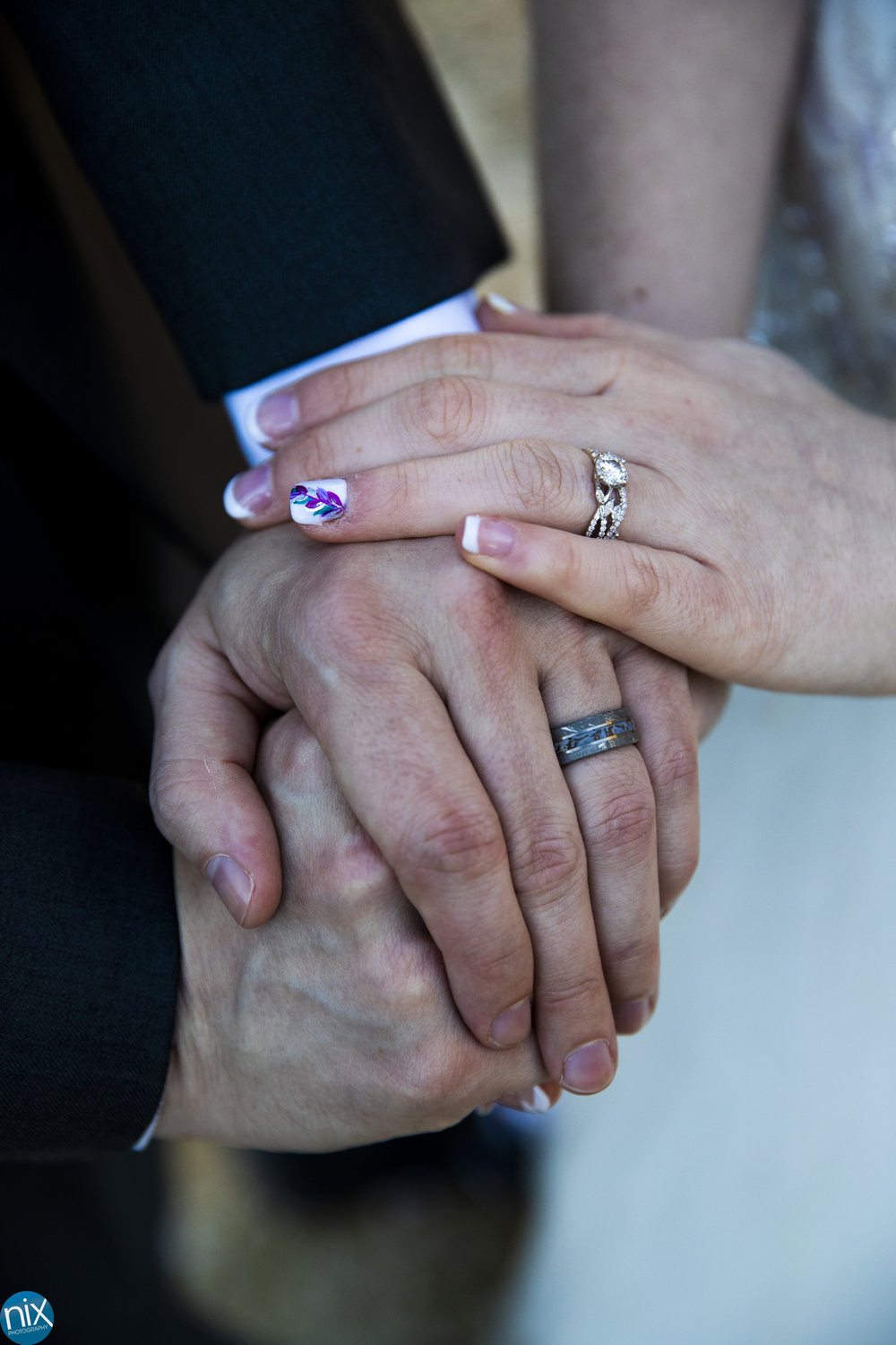 bride and groom hold hands with wedding rings.jpg