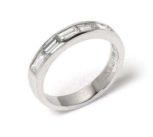 Baguette cut diamonds channel-set into white gold band.