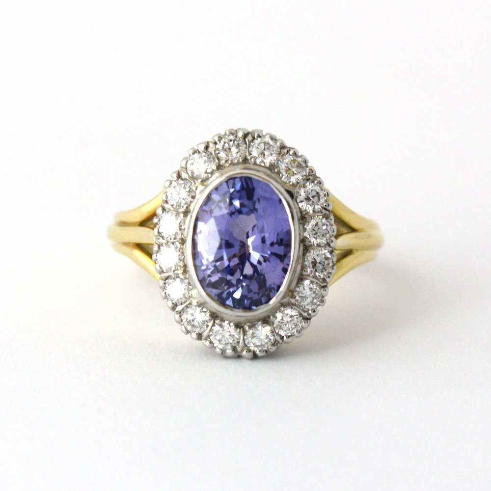 Yellow and white gold oval ceylon sapphire with diamond halo and organ pipe shoulders.