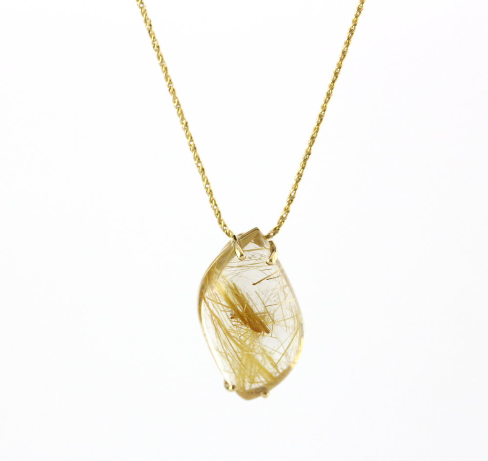 Fancy cut cabochon rutilated quartz pendant with yellow gold necklace.