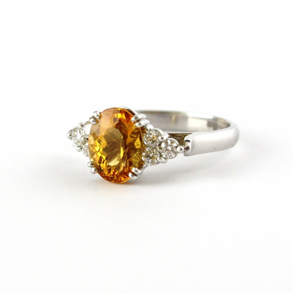 Double claw-set Imperial topaz with 6 round diamonds claw-set shoulders in white gold.