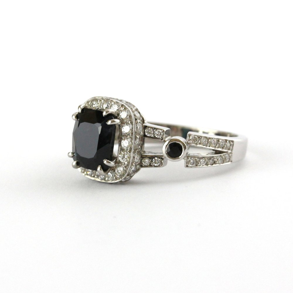Cushion cut Australian sapphire with diamond halo and shoulders, and two black diamonds set in white gold ring.