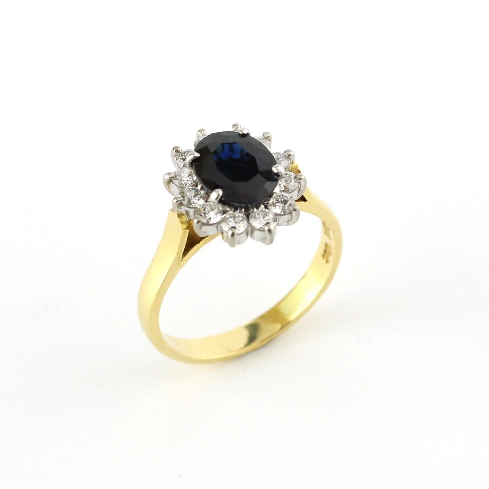 Sapphire with diamond halo set in white and yellow gold ring.