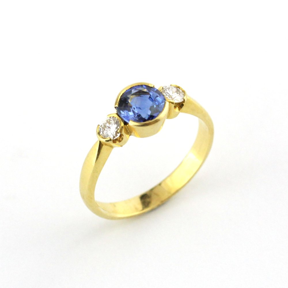 Half bezel set sapphire and diamonds in yellow gold.