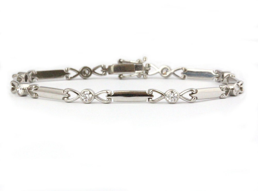 White gold bracelet with heart links and bezel set diamonds.