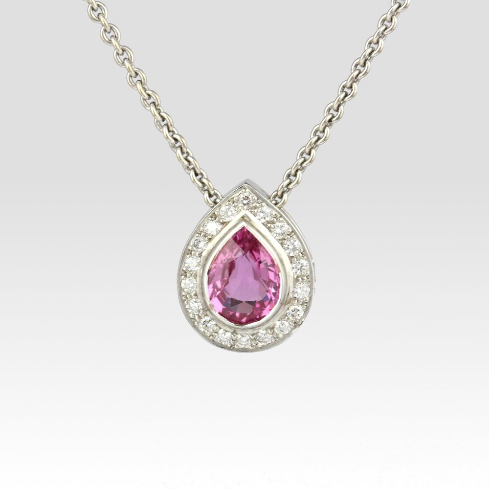 Teardrop shaped pink sapphire with diamonds surrounding in white gold.