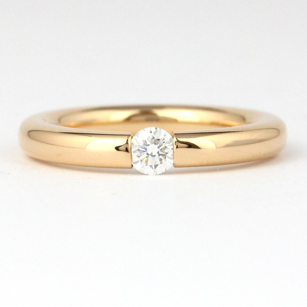 Round profile rose gold band with tension look end set diamond.