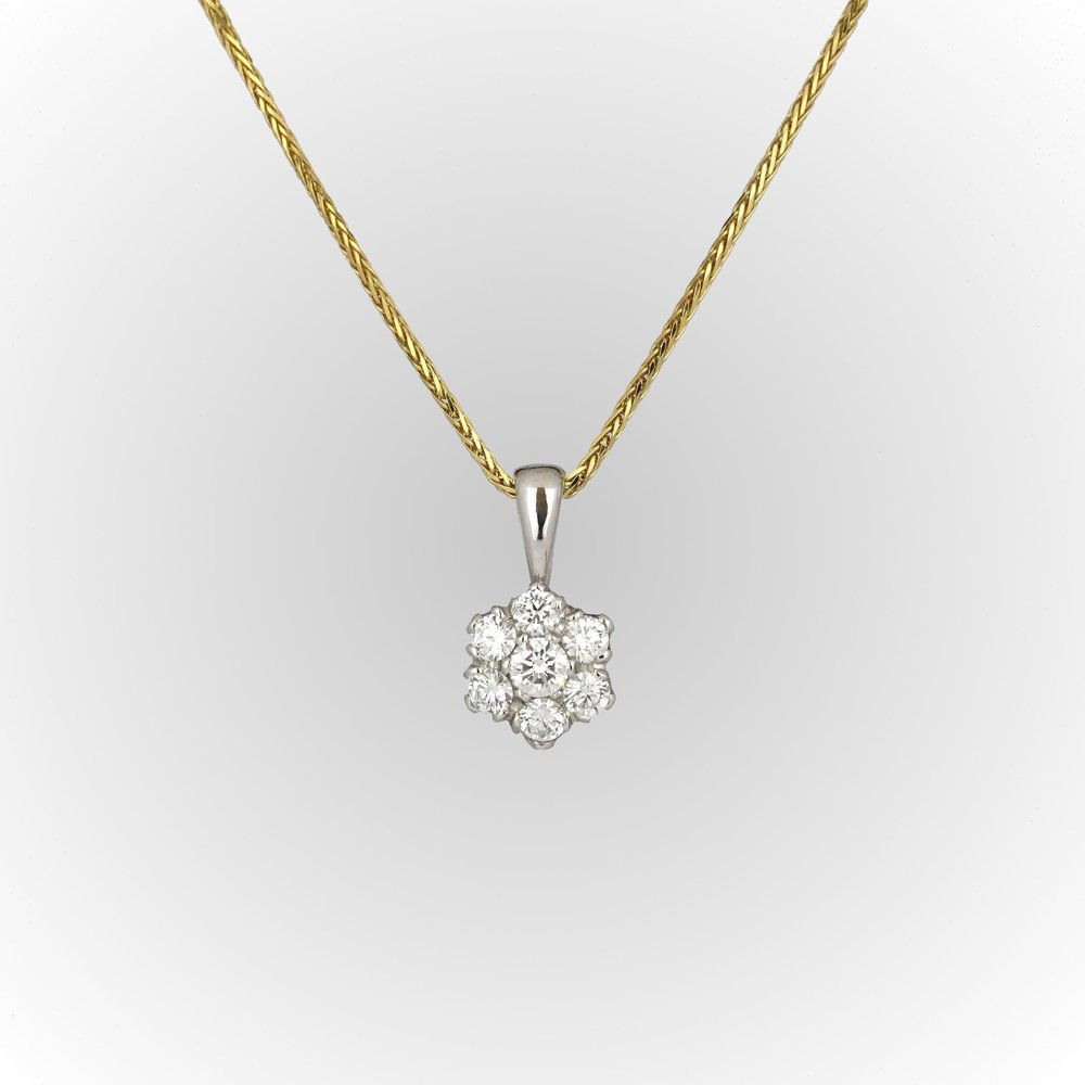 White gold diamond cluster pendant on yellow gold chain.