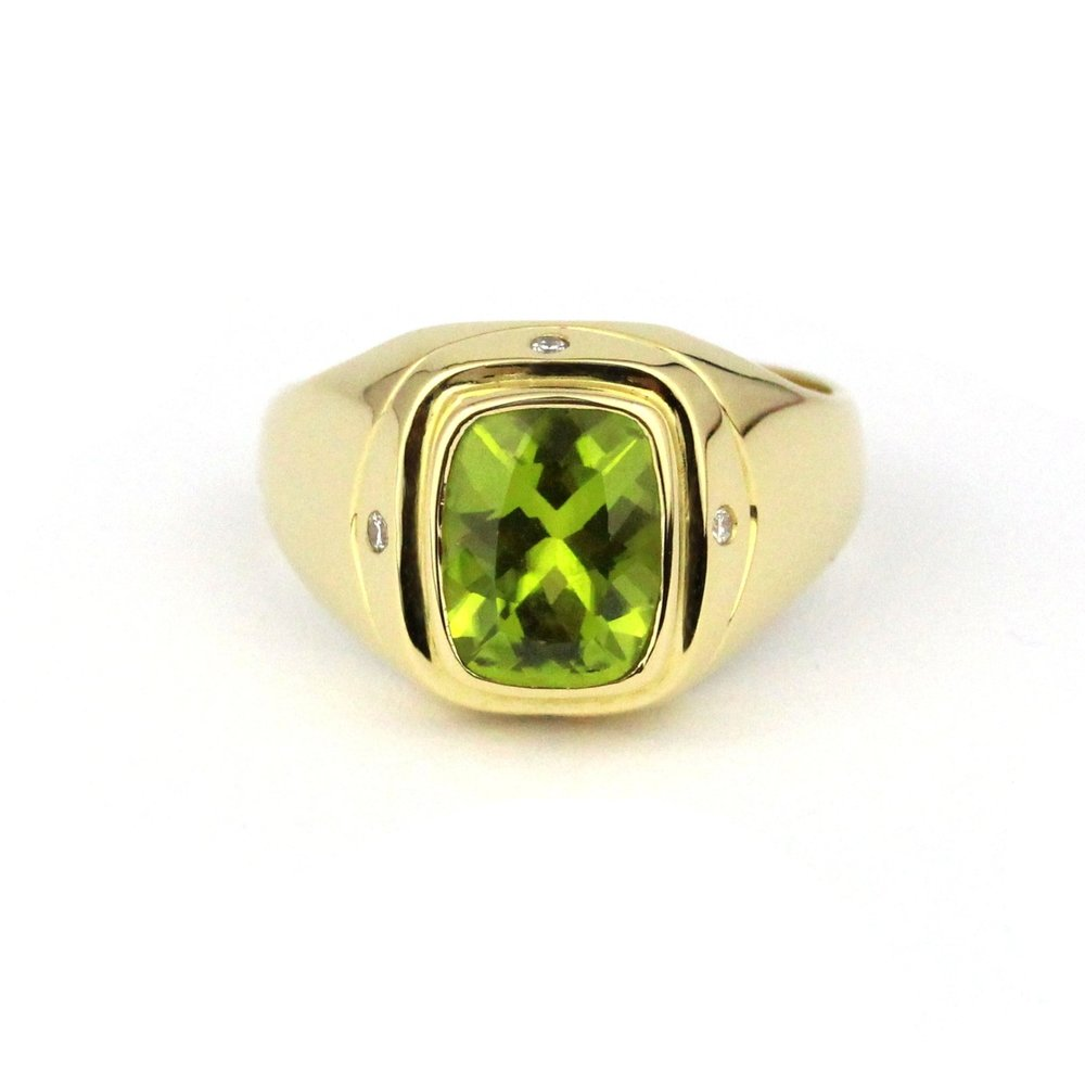 Rectangle cushion cut peridot bezel set in yellow gold ring with gypsy set diamonds.
