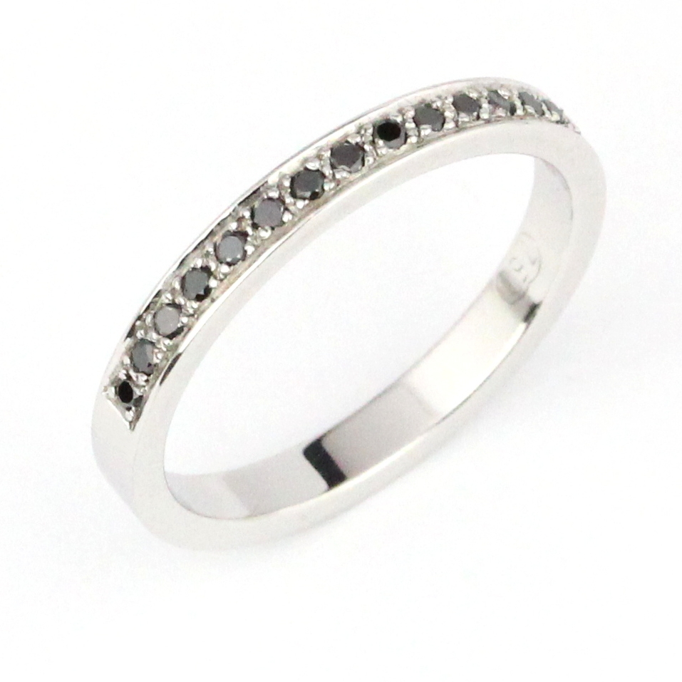 Black round diamonds grain set into white gold band.