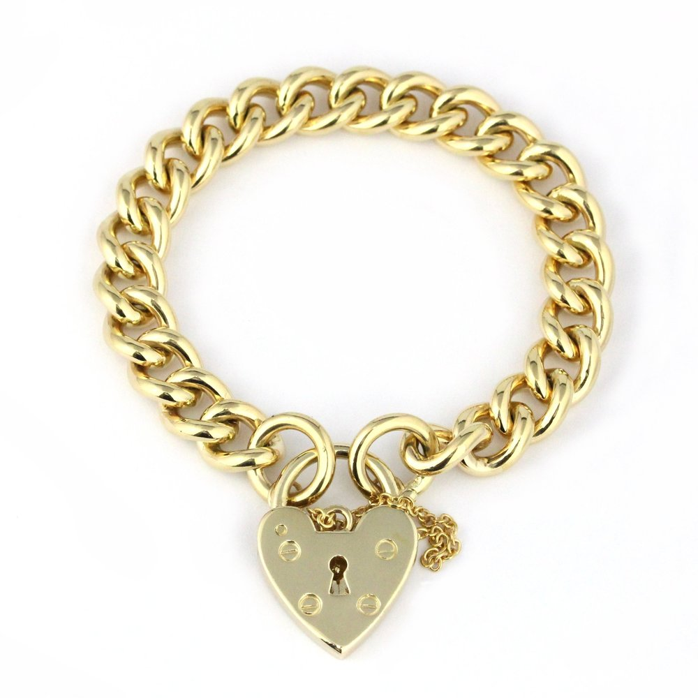 Yellow gold curb link bracelet with heart padlock clasp and safety chain.