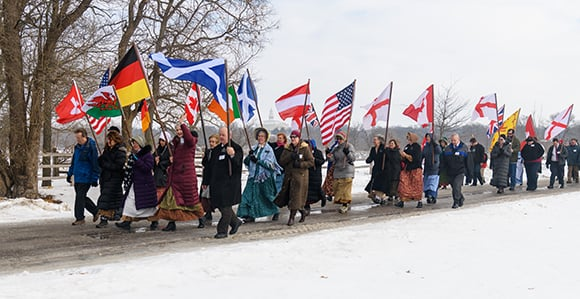 Members and missionaries walk down Main and Parley Streets in Nauvoo on February 2, 2019, to commemorate the 1846 Nauvoo Exodus. The flags represent many of the nationalities of those who lived in Nauvoo in the 1840s. Photo courtesy of Bruce Cornwell.