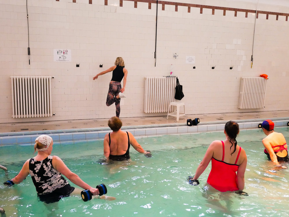 Här pågår den märkligaste vattengymnastiken jag beskådat. Instruktören såg inte det minsta intresserad ut av vad hon gjorde. Men alla i poolen verkade nöjda och glada.