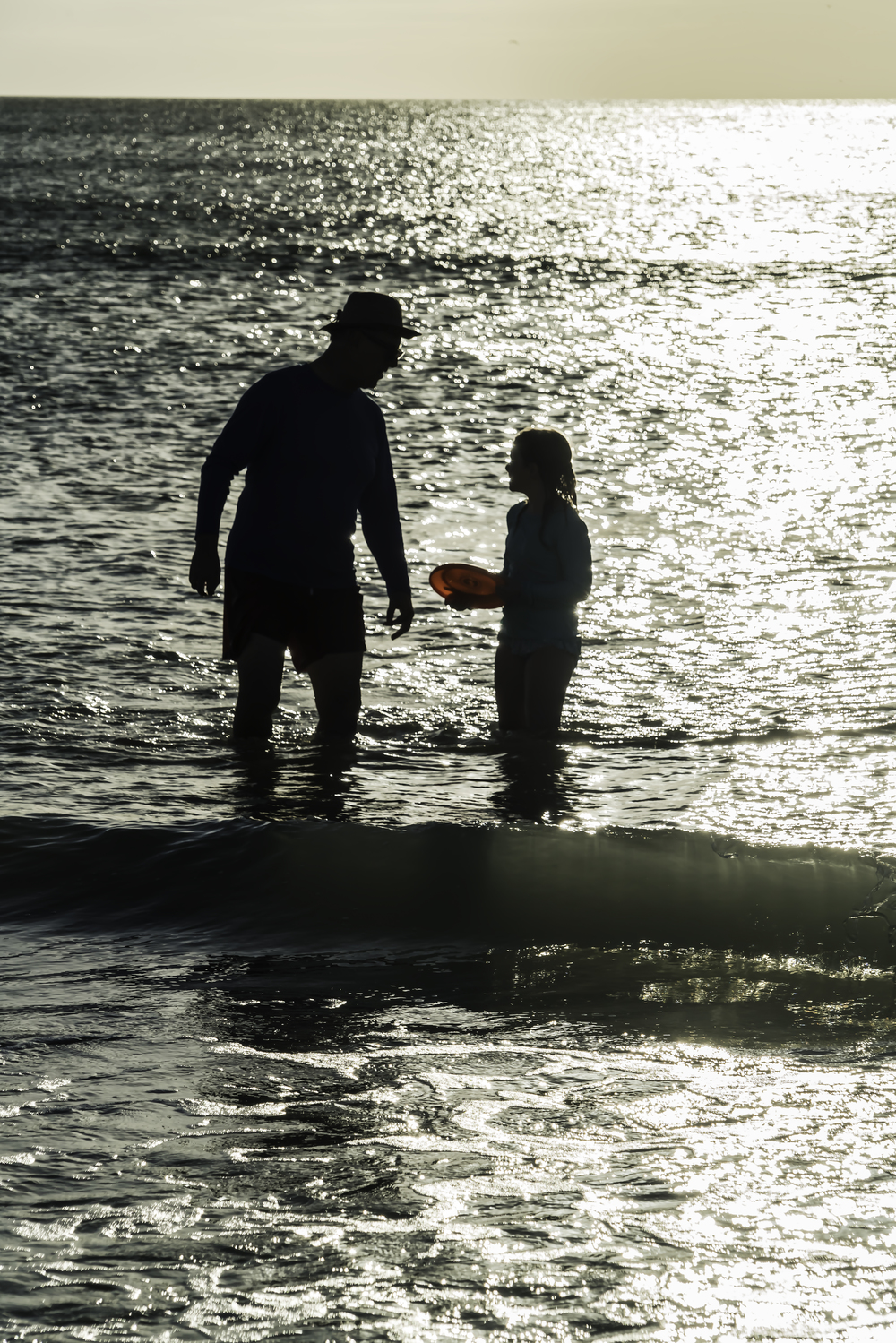 Man and girl in the gulf in Naples FL, late afternoon.  Frisbee included.