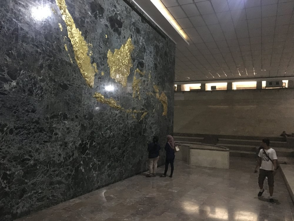 This is the room around the elevator to the top. There is stadium style seating around the inner shaft, and a large gold map of Indonesia on the marble wall.