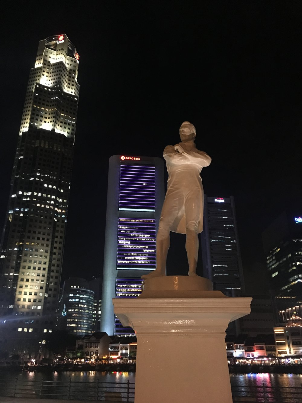 A statue of Thomas Raffles in front of the Raffles Tower