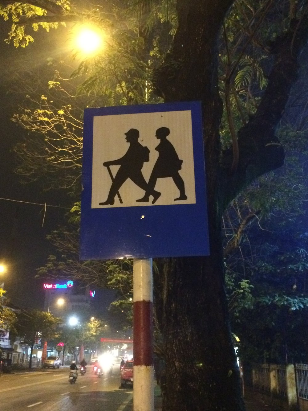 A crossing sign in Hue, Vietnam - are we supposed to identify with the silhouettes of these people? Hmmmmm. If you are not riding a motor scooter, I guess they assume you are a hitch hiker. Hue, Vietnam.
