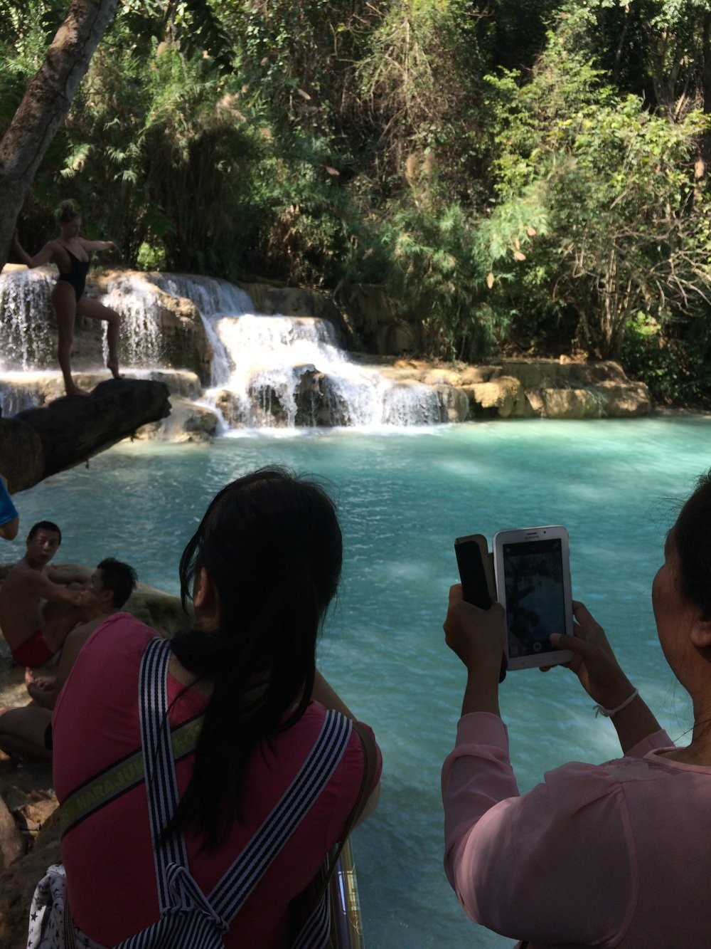 These Chinese tourists came to take pictures of american girls modeling, and there happens to be a waterfall in the background too. Kuang Si Waterfall, Loas.