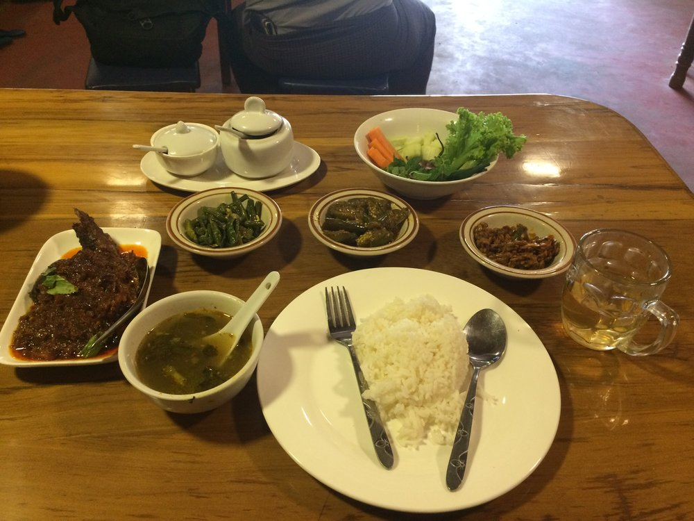 A Burmese meal in Mandalay, Myanmar. Pickled side dishes, soup, and catfish curry.