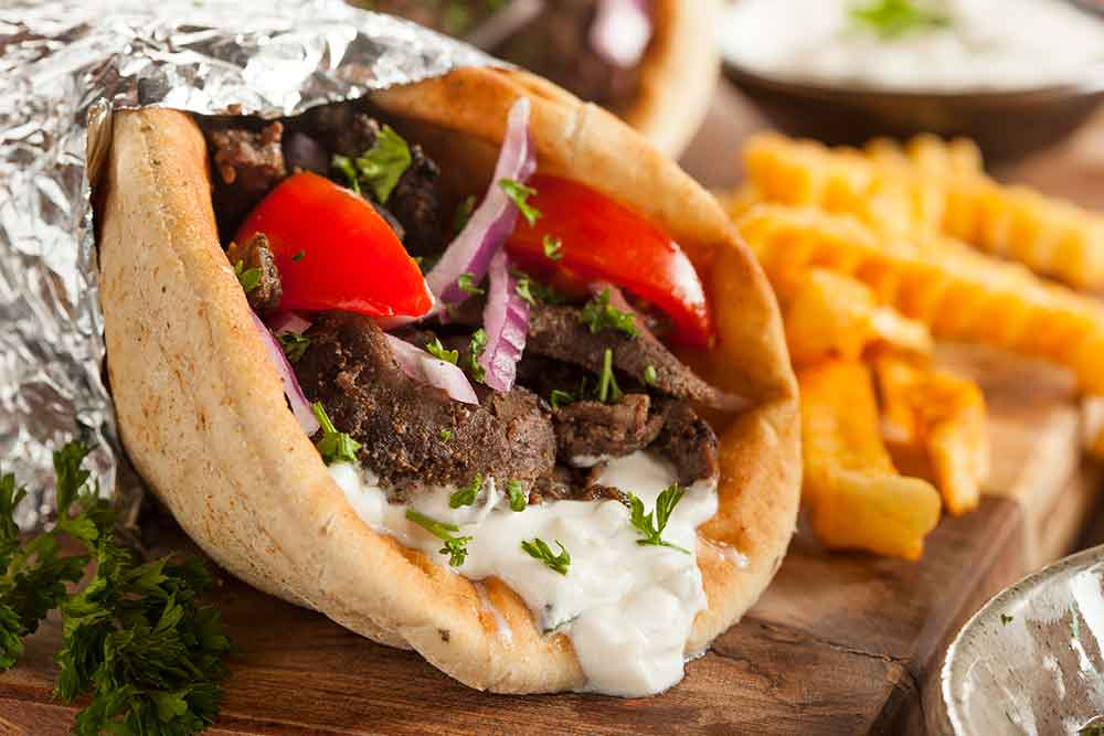 Gyro  a Greek dish made of meat cooked on a vertical rotisserie, beef and lamb, and usually served in a pita or sandwich, with tomato, onion, and tzatziki sauce (a Greek sauce made of yogurt, cucumber, and mint)