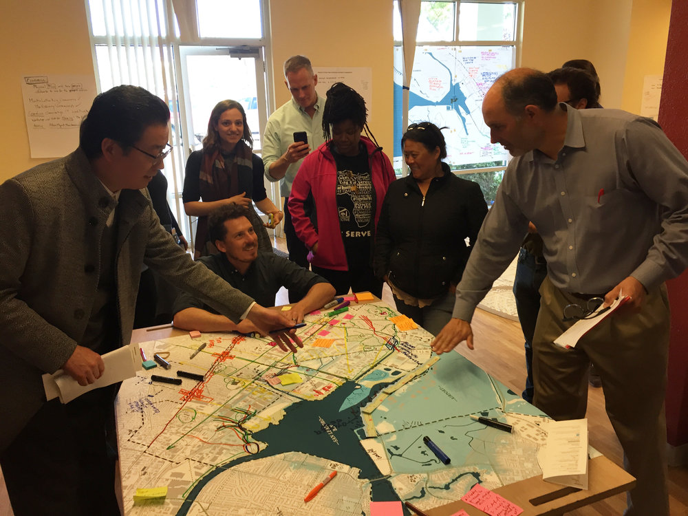 Participants gather around a table map to share ideas for the future of San Leandro Bay