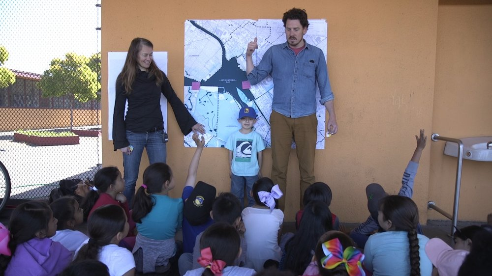 Claire and Nico (6ft) and kid (3ft) talking about SLR with a group of primarily Hispanic 6-7 year olds
