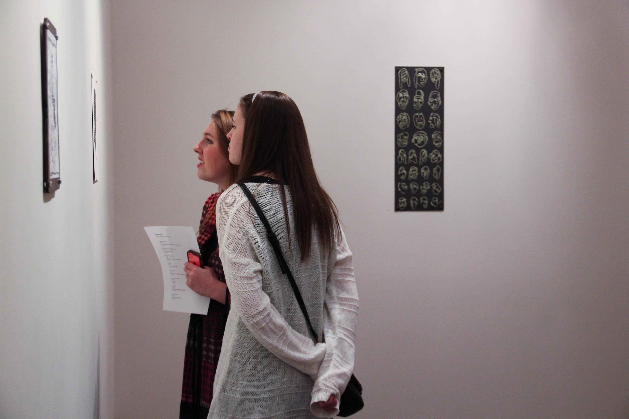 Sophomores Shayla Dougherty and Lexington Johnson enjoy the art presented in the Junior Art Show_Johnson