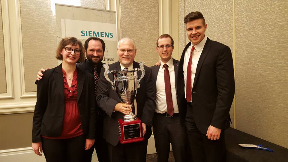 Ethics Bowl team members Kaitlin Barnes, James Eccles, co-coach Mike Ingram, Brennan Neal and TJ Westre hold the nationals trophy. Not pictured: team member Ellie Probus and co-coach Keith Wyma.