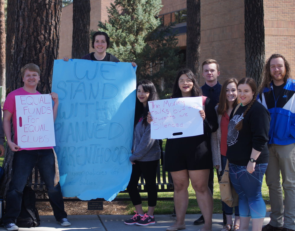 Students hold signs at a protest against Beck Taylor's position on Planned Parenthood. Photo by Kelly Logie