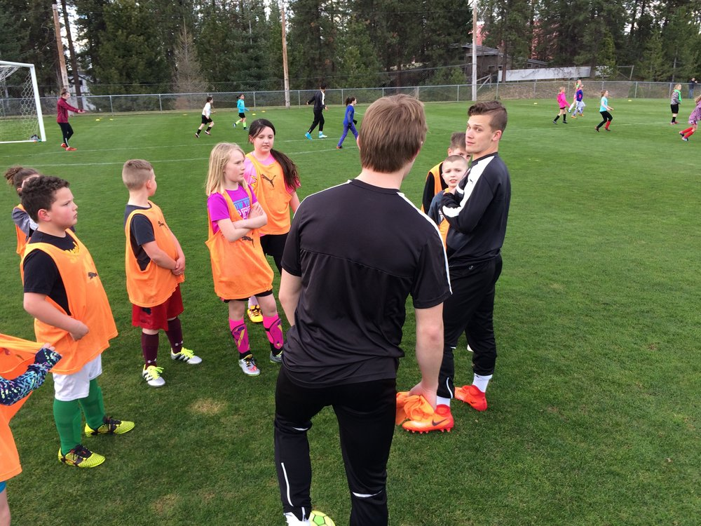 Christian Haas, '19, (left) and Jonah Snyder, '18, (right) work with local children at the Whitworth Soccer clinic on April 6.