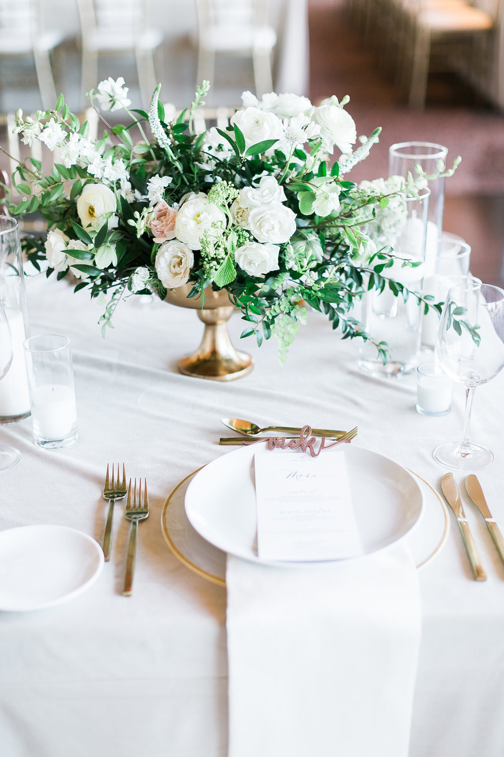 Gold compote vase filled with overflowing greenery and white florals