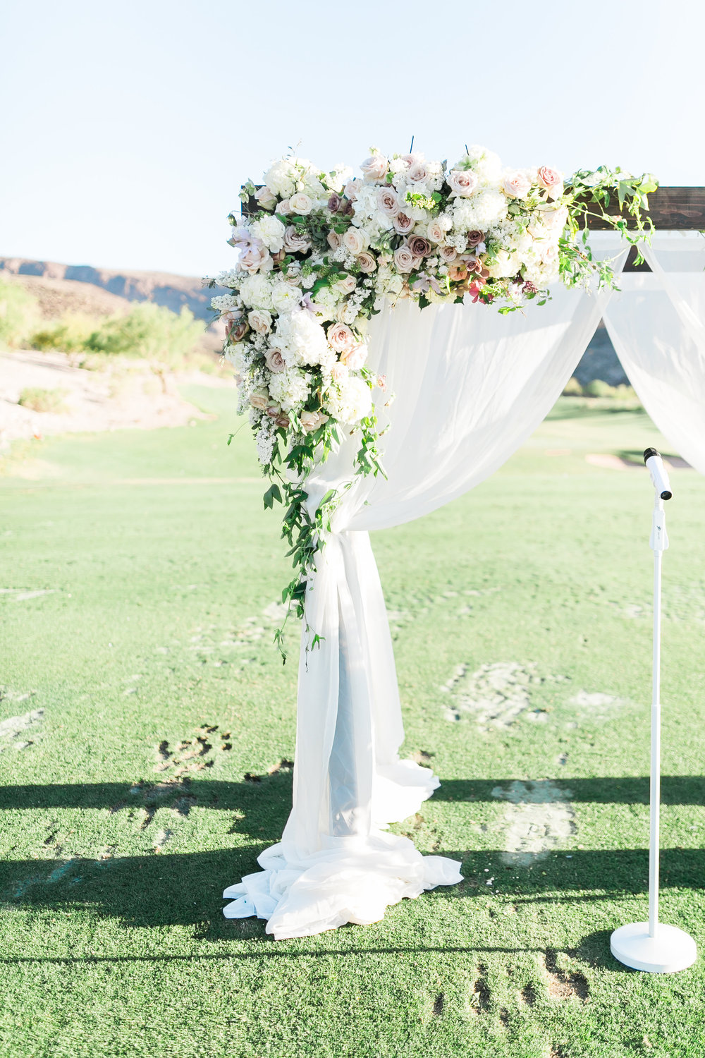 Asymmetrical florals on wedding arbor. Colorado wedding floral designer, Layers of Lovely