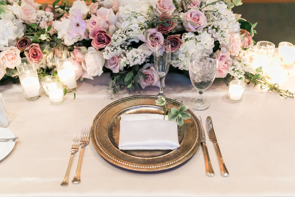 Long, low floral arrangement for the sweetheart table.