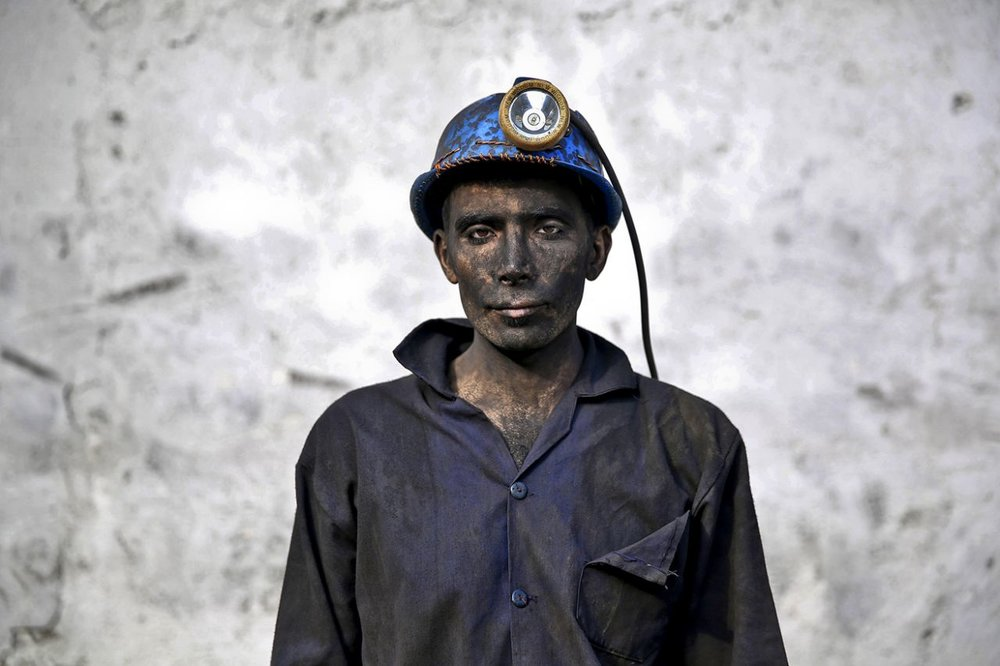An Iranian coal miner with his face smeared black from coal poses for a photograph at a mine near the city of Zirab 132 miles northeast of the capital Tehran, on a mountain in Mazandaran province, Iran on May 7, 2014. (Photo: Ebrahim Noroozi/AP)